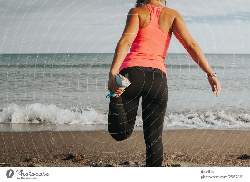 Leg stretching in front of the sea. Sports girl. Lifestyle Body Athletic Fitness Wellness Leisure and hobbies Beach Sports Training Jogging Human being Feminine