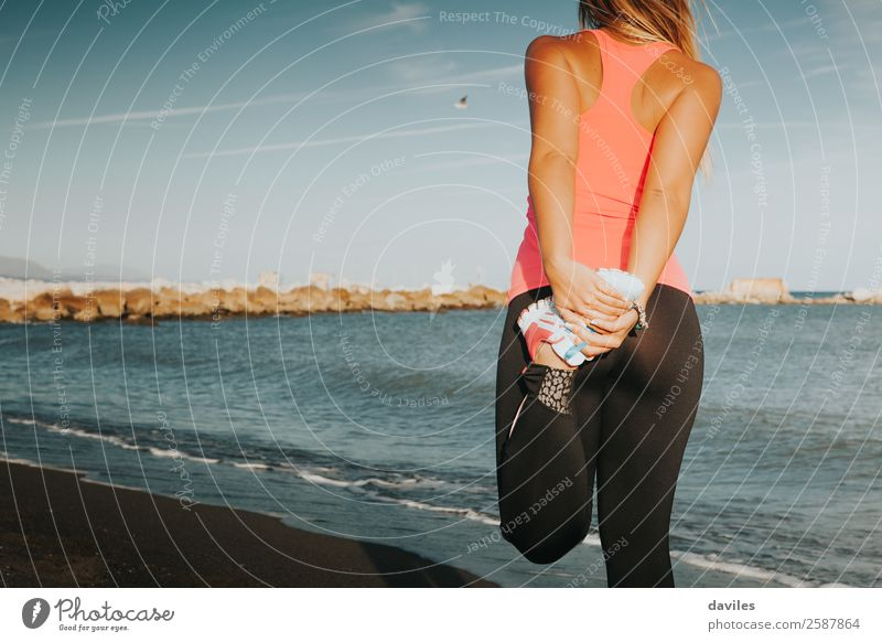 Sports girl stretching legs on the beach, with sea in the background. Lifestyle Body Summer Beach Ocean Fitness Sports Training Jogging Human being Feminine