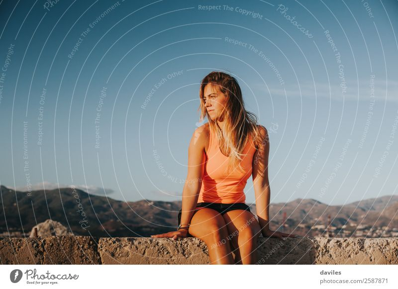 Beautiful woman with sports clothes, sitting on a concrete wall outdoors at sunset. Lifestyle Sun Mountain Sports Fitness Sports Training Human being Feminine