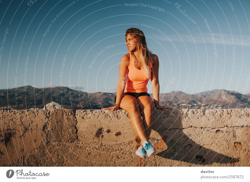 Beautiful woman with sports clothes, sitting on a concrete wall outdoors at sunset. Lifestyle Body Athletic Wellness Well-being Sun Mountain Sports Fitness