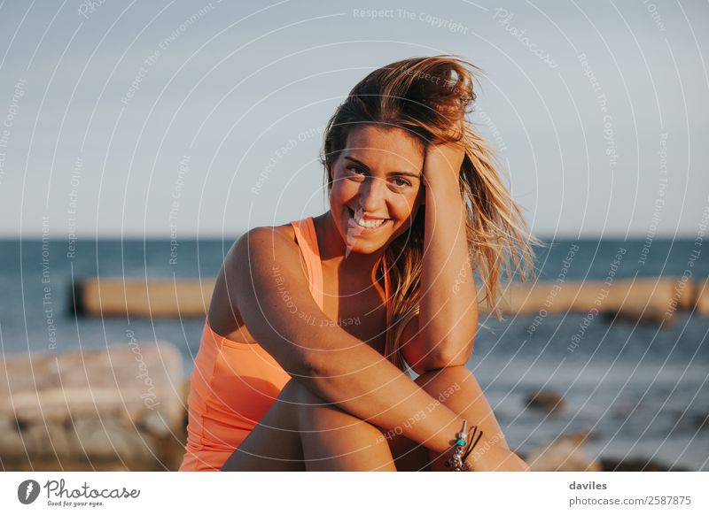 Beautiful woman with sports clothes, sitting on a concrete wall outdoors at sunset. Lifestyle Joy Body Wellness Relaxation Sun Ocean Sports Fitness