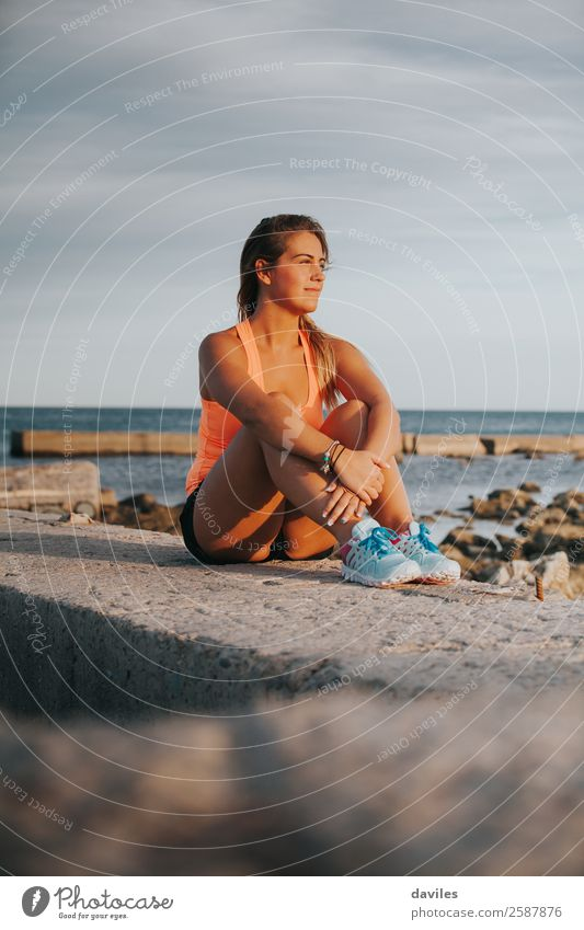 Beautiful woman with sports clothes, sitting on a concrete wall outdoors at sunset. Lifestyle Joy Wellness Relaxation Sun Ocean Sports Fitness Sports Training