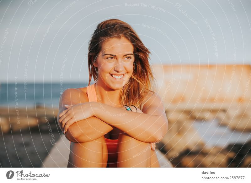 Beautiful woman with sports clothes, sitting on a concrete wall outdoors at sunset. Lifestyle Joy Body Wellness Relaxation Leisure and hobbies Sun Sports