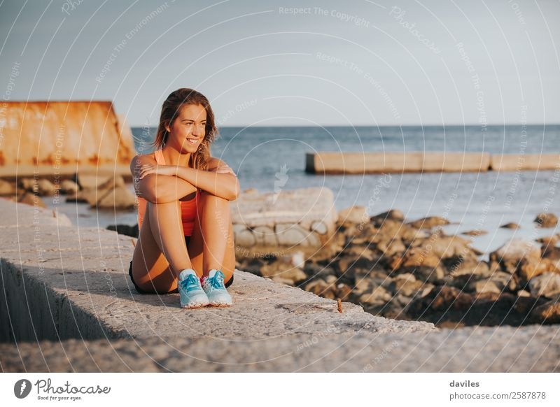 Smiling woman with sports clothes, sitting on a concrete wall outdoors at sunset. Lifestyle Joy Happy Beautiful Body Relaxation Leisure and hobbies Ocean Sports