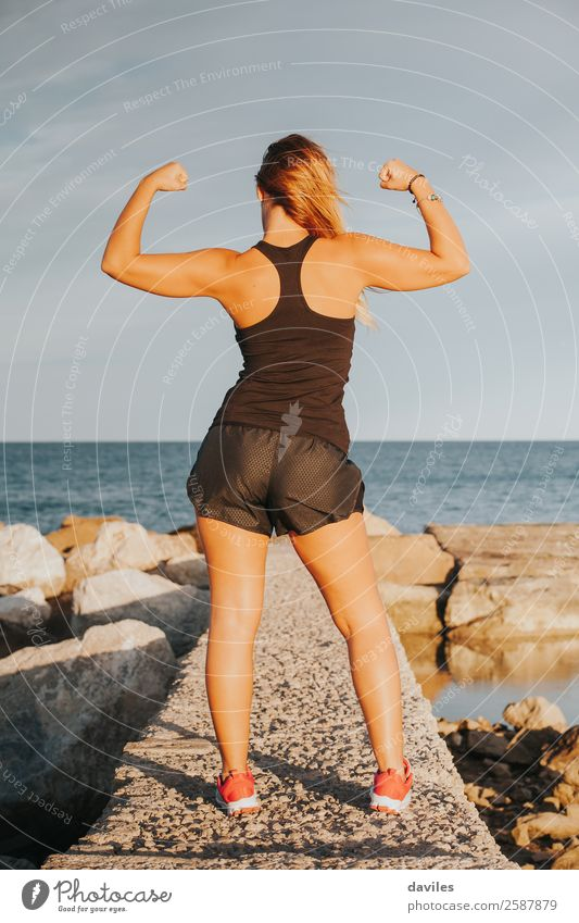 Young girl showing strong biceps after outdoors fitness workout. Fitness woman. Whole body back view. Joy Happy Beautiful Body Summer Beach Sports Success