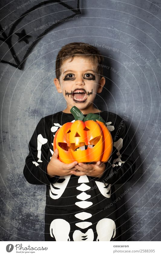 Young boy in the Skeleton costume holding Halloween pumpkin Joy Beautiful Face Life Decoration Feasts & Celebrations Carnival Hallowe'en Child Internet