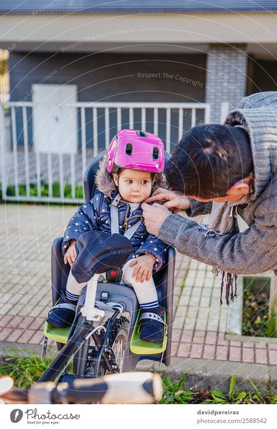 Father closing helmet to her daughter sitting in bike seat Lifestyle Leisure and hobbies Vacation & Travel Trip Chair Cycling Child Baby Toddler Man Adults