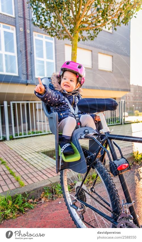 Little girl with security helmet sitting in bike seat Lifestyle Leisure and hobbies Vacation & Travel Trip Chair Sports Child Baby Toddler Woman Adults