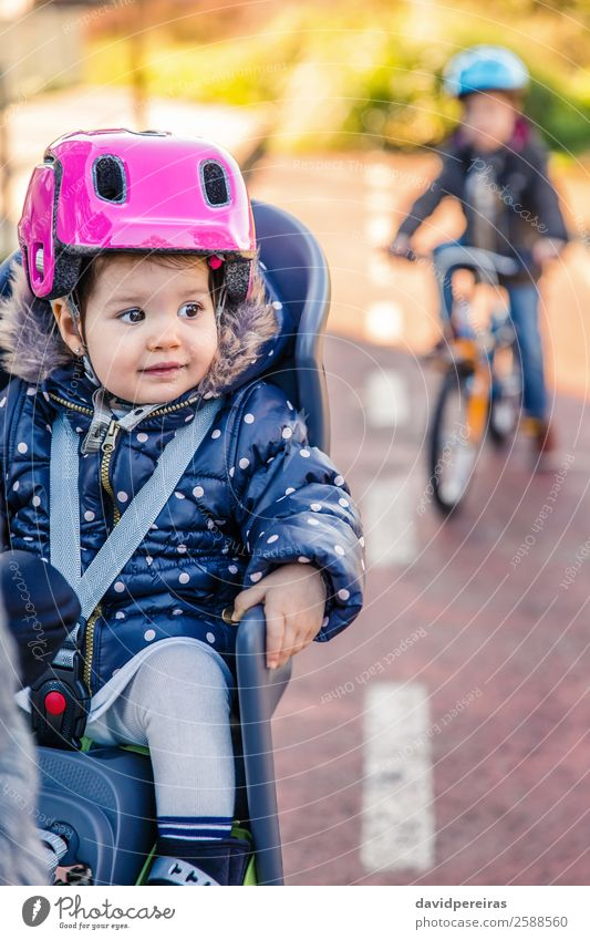 Lttle girl with helmet on head sitting in bike seat Lifestyle Leisure and hobbies Vacation & Travel Trip Winter Chair Child Baby Toddler Woman Adults