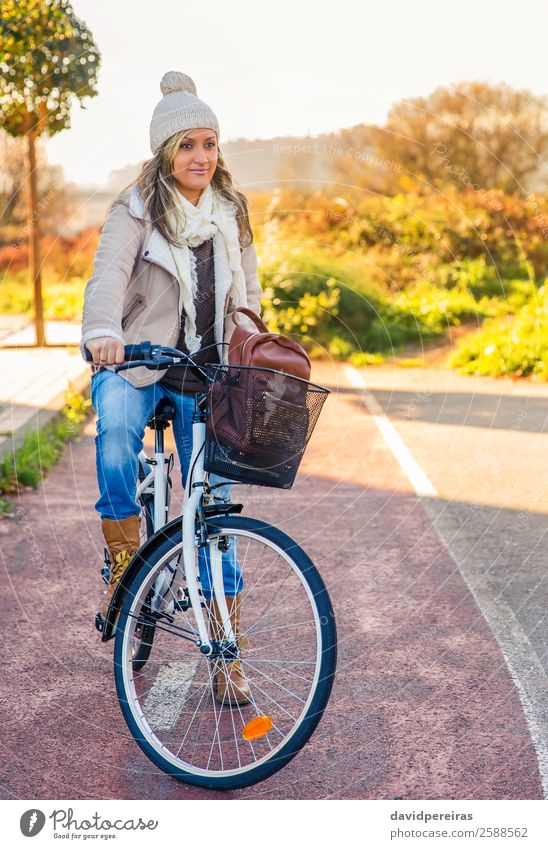 Young woman sit over bicycle in a street bike lane Lifestyle Happy Beautiful Relaxation Leisure and hobbies Sun Winter Sports Cycling Human being Woman Adults