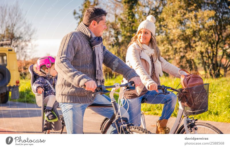 Family with little daughter sitting on bike seat riding bicycles Lifestyle Happy Relaxation Leisure and hobbies Vacation & Travel Sun Winter Sports Child Baby