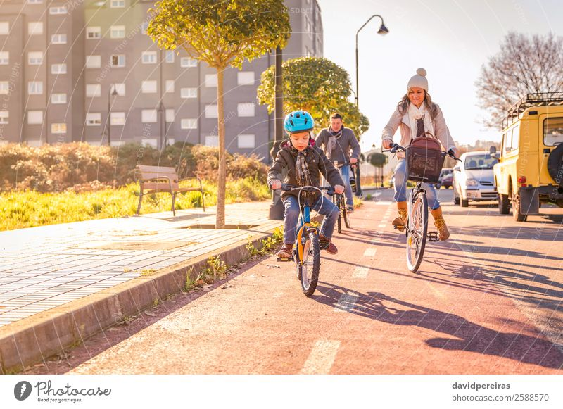 Happy family with a child riding bicycles by the city Lifestyle Relaxation Leisure and hobbies Vacation & Travel Sun Winter Sports Child Boy (child) Woman