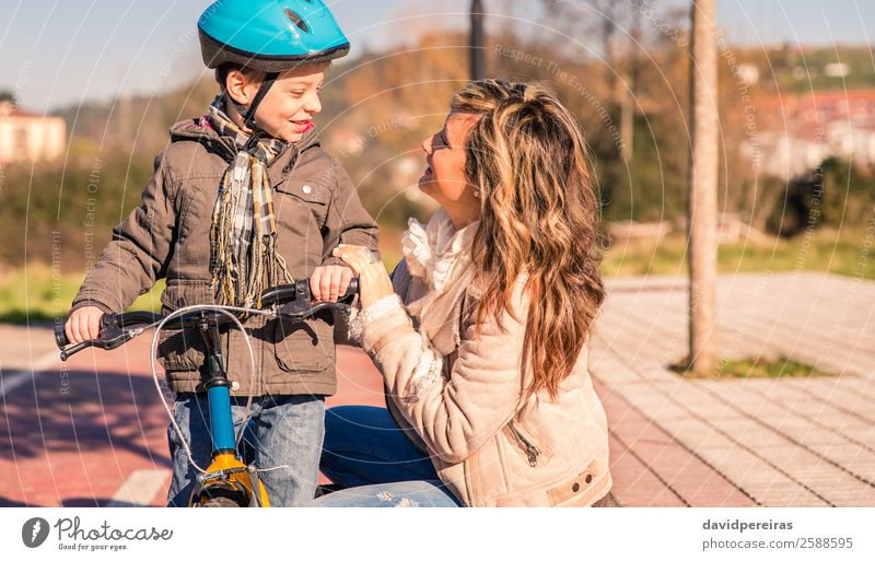 Happy young mother with her son stand over bicycle Lifestyle Relaxation Leisure and hobbies Vacation & Travel Sun Winter Sports Child Boy (child) Woman Adults