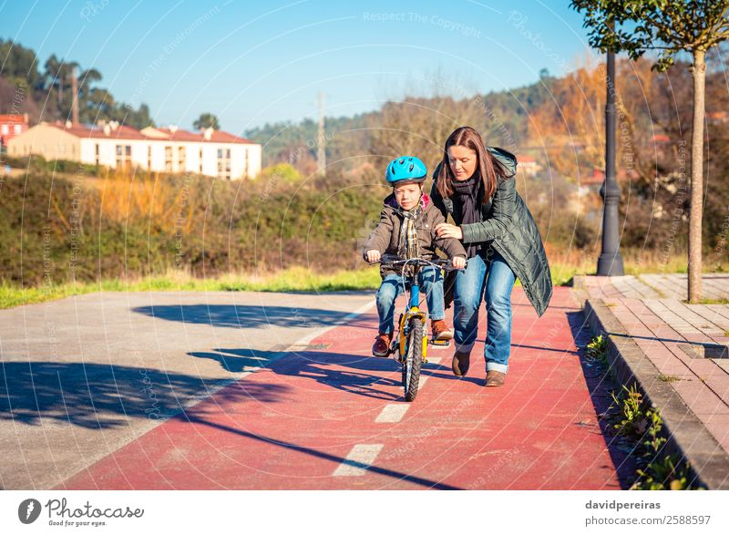Mother teaching her son to ride a bicycle Lifestyle Joy Happy Leisure and hobbies Playing Sun Winter Sports Success Cycling Child School Boy (child) Woman