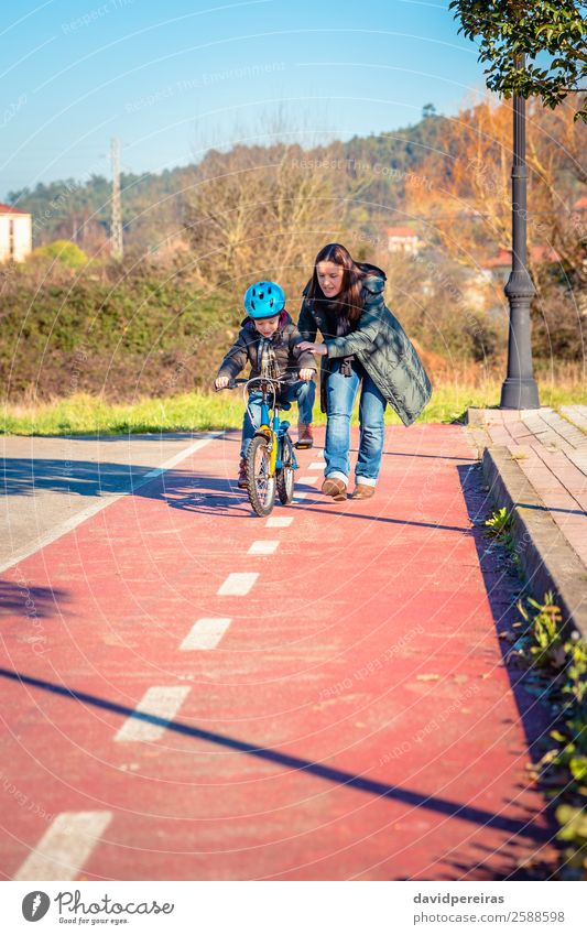 Mother teaching her son to ride a bicycle Woman Child Nature Man Sun Joy Winter Street Lifestyle Adults Lanes & trails Sports Family & Relations Happy