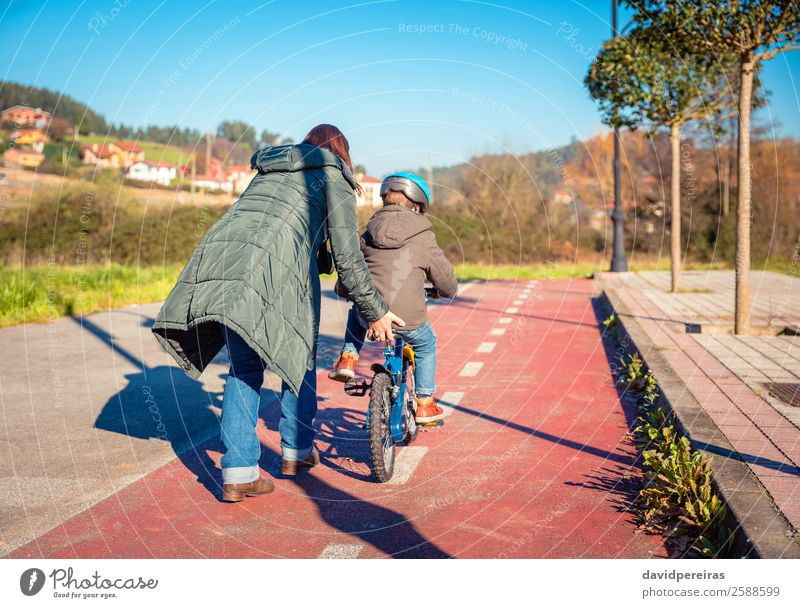 Back view of mother teaching her son to ride a bicycle Lifestyle Joy Happy Leisure and hobbies Playing Sun Winter Sports Cycling Child School Boy (child) Woman