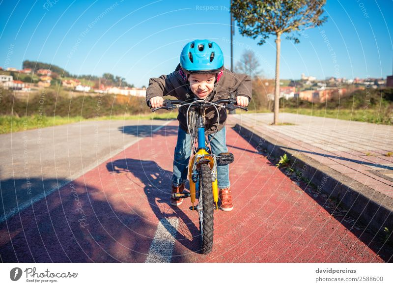 Portrait of boy with defiant gesture over his bike ready to run Lifestyle Joy Happy Face Leisure and hobbies Playing Sun Winter Sports Cycling Child Human being