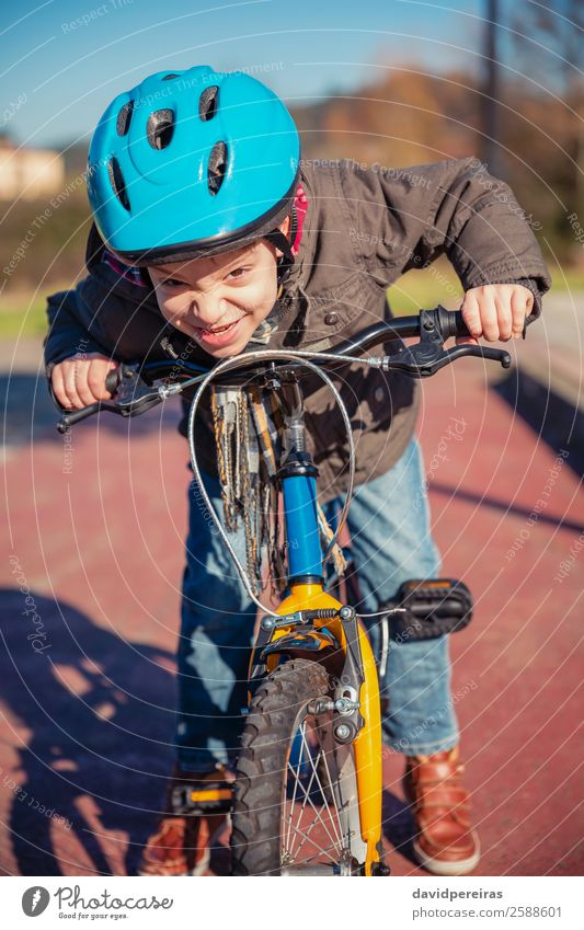 Naughty boy with defiant gesture over his bike Lifestyle Happy Face Leisure and hobbies Playing Sun Winter Sports Cycling Child Human being Boy (child) Street