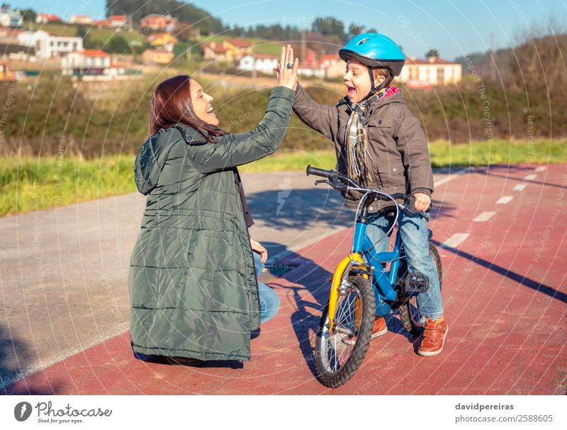 Mother and son giving five in the learn to ride a bicycle Lifestyle Joy Happy Leisure and hobbies Playing Sun Winter Sports Success Cycling Child School