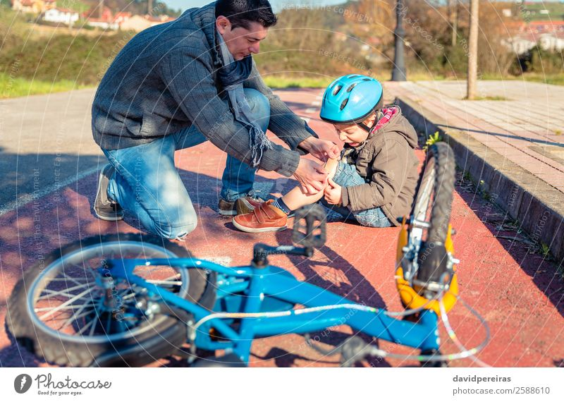 Father putting a plaster band over knee injury to son Medication Sports Cycling Child Boy (child) Man Adults Band Street Lanes & trails Scream Sadness Cry