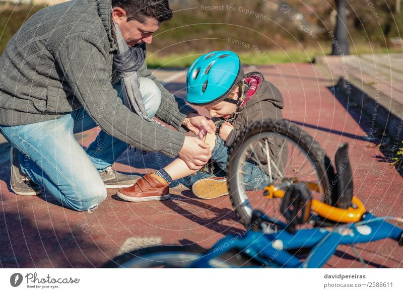 Father putting plaster band over knee injury to his son Medication Sports Child Boy (child) Man Adults Street Lanes & trails Scream Sadness Cry Protection Pain