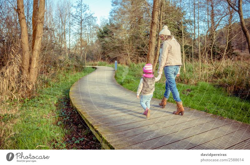 Back view of mother and daughter walking over a wooden pathway Lifestyle Joy Happy Calm Leisure and hobbies Freedom Winter Child Woman Adults Parents Mother