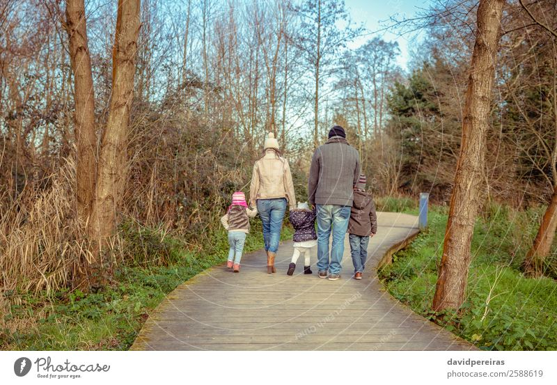Back view of family walking together over a wooden pathway Lifestyle Joy Happy Leisure and hobbies Winter Child Boy (child) Woman Adults Man Parents Mother