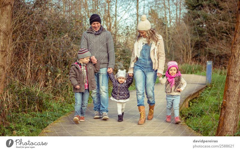 Happy family walking together over a wooden pathway Lifestyle Joy Leisure and hobbies Winter Child Boy (child) Woman Adults Man Parents Mother Father Sister