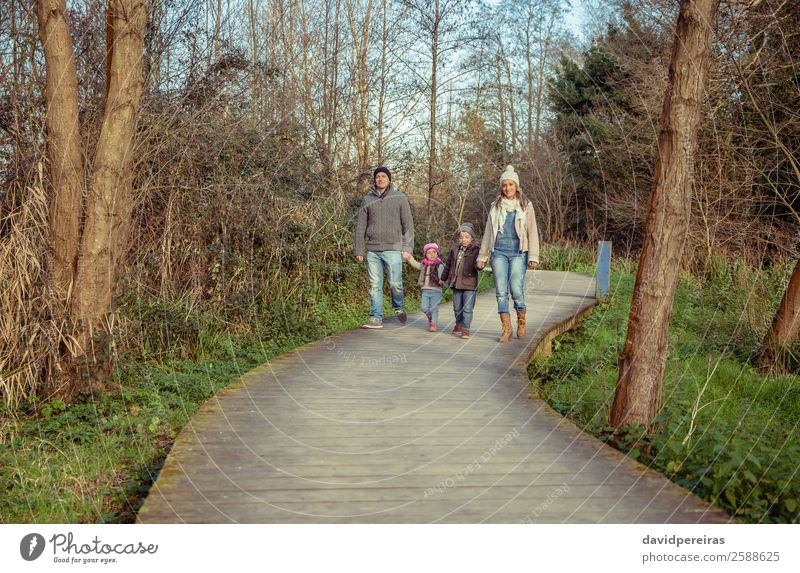 Happy family walking together holding hands in the forest Woman Child Human being Nature Vacation & Travel Man Beautiful Green Landscape Hand Tree Forest Winter