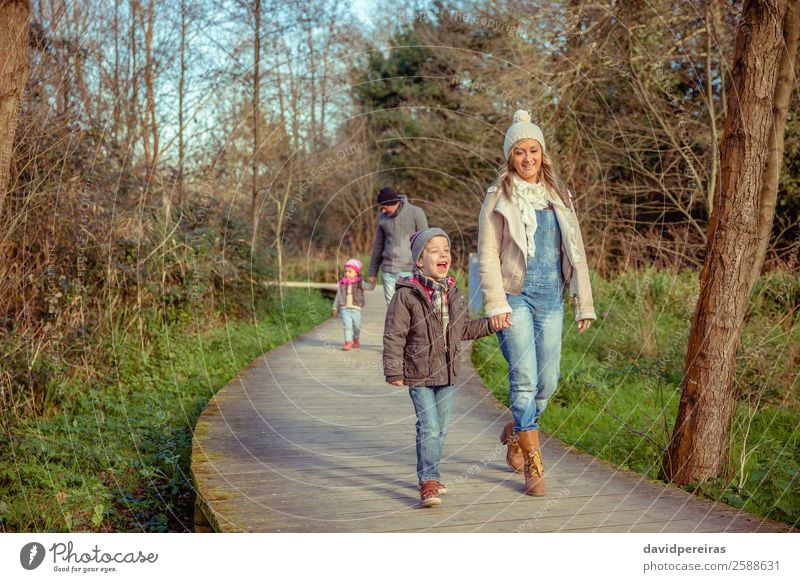 Happy family walking together over a wooden pathway Woman Child Nature Man Green Hand Tree Joy Forest Winter Lifestyle Adults Autumn Wood Environment Love