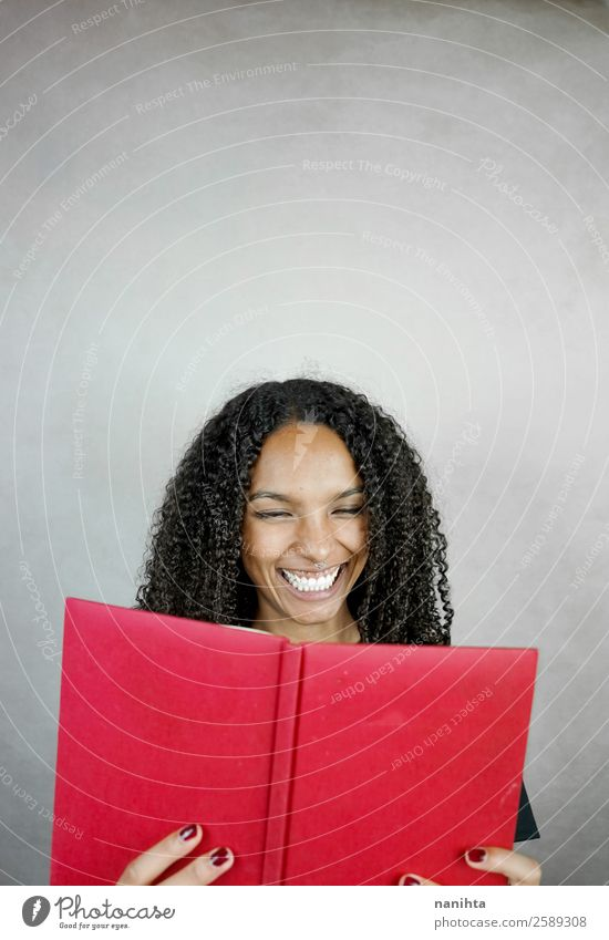 Young happy woman reading a red book Joy Leisure and hobbies Education Study Student Human being Feminine Young woman Youth (Young adults) Woman Adults 1