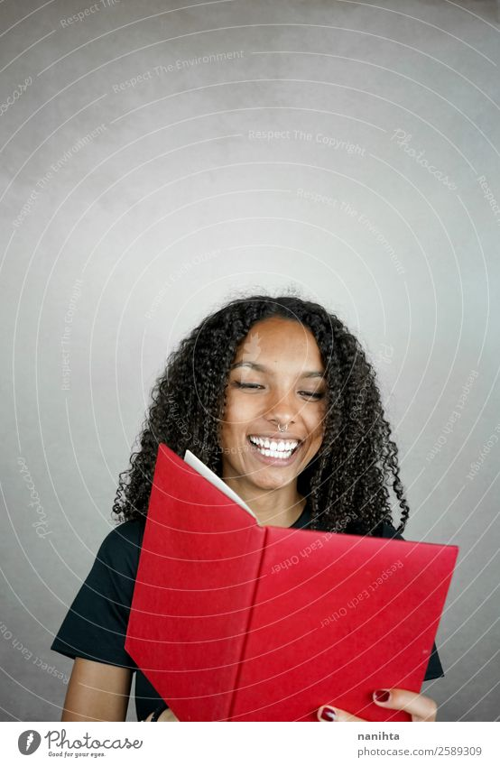 Young happy woman reading a red book Woman Human being Youth (Young adults) Young woman Red Joy Black Lifestyle Adults Feminine Laughter Hair and hairstyles