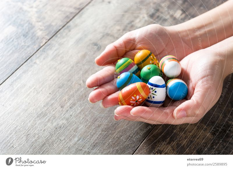 Hands showing Easter eggs, on wooden table. Vacation & Travel Decoration Feasts & Celebrations Spring Flower Tulip Wood Colour Tradition Indicate Egg Festive