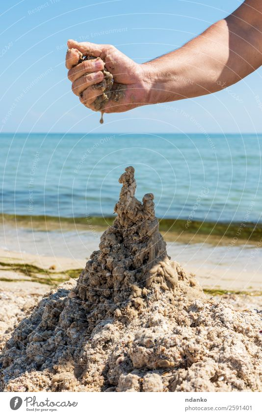 castle from the wet sea sand Joy Relaxation Playing Vacation & Travel Tourism Summer Sun Beach Ocean Hand Nature Landscape Sand Sky Coast Castle Drop Build Blue