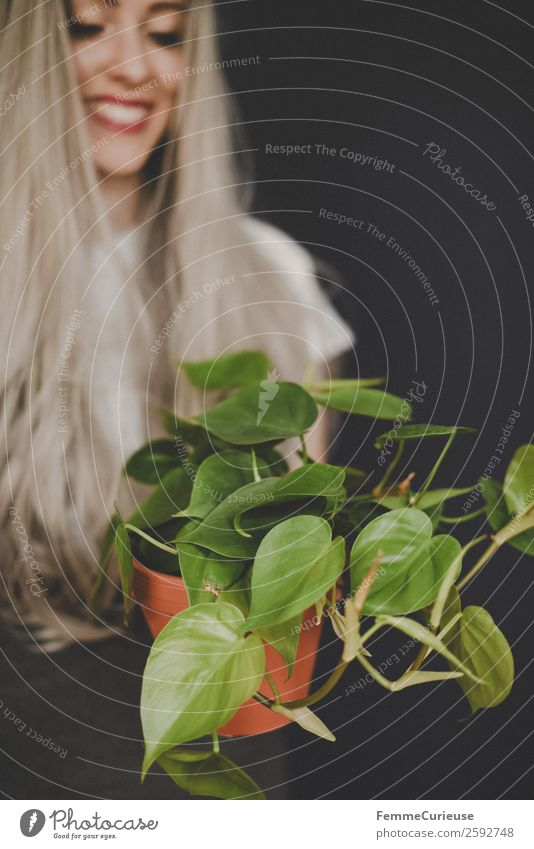 Young smiling woman with long hair showing a plant Lifestyle Elegant Style Design Feminine Young woman Youth (Young adults) Woman Adults 1 Human being