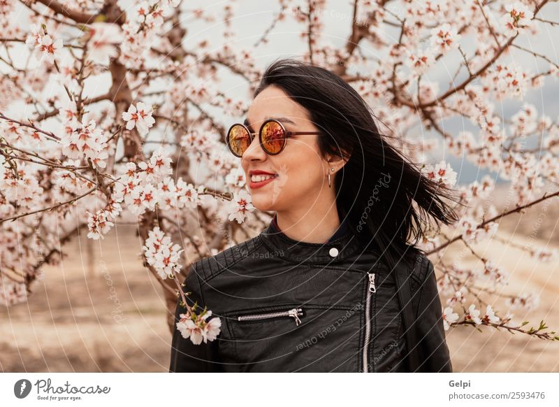 Pretty brunette girl Style Happy Beautiful Face Garden Human being Woman Adults Nature Tree Flower Blossom Park Fashion Jacket Leather Sunglasses Brunette