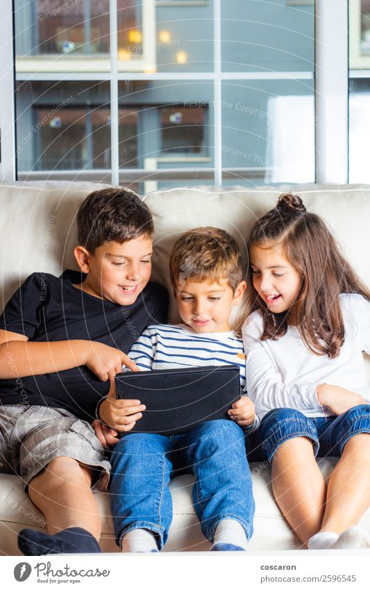 Three kids using a tablet at home Lifestyle Joy Happy Beautiful Leisure and hobbies Playing Sofa Education Child Study Student Cellphone Computer Notebook