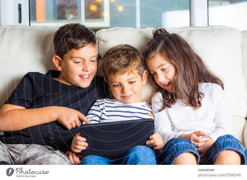 Three kids using a tablet at home Lifestyle Joy Happy Beautiful Leisure and hobbies Playing Sofa Education Child Study Cellphone Computer Notebook Screen