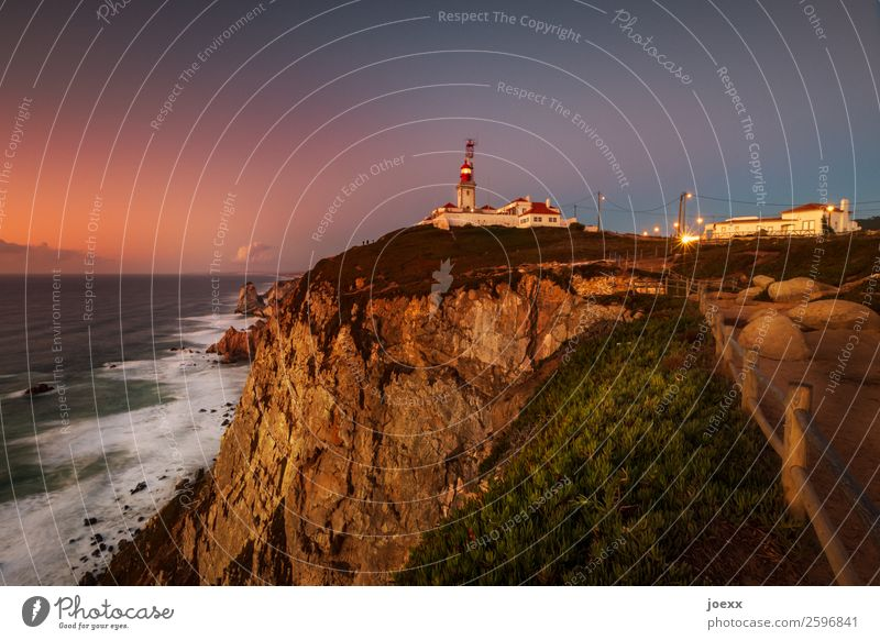 Lighthouse on steep rocky coast with sea and waves and spray before dusk Ocean Rock Waves Landscape Sky houses Horizon Beautiful weather Portugal Exterior shot