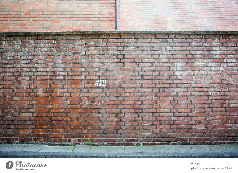 Cologne Deserted Wall (barrier) Wall (building) Facade Brick Fascist Against Stone Sign Characters Moody Discordant Contempt Animosity Defiant Society