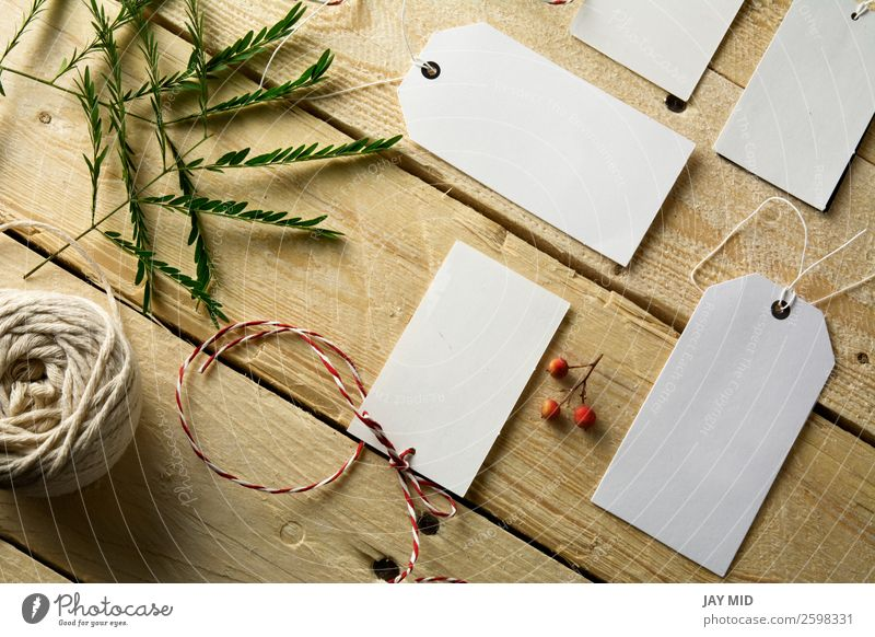 Set of empty paper price tags, wooden background - a Royalty