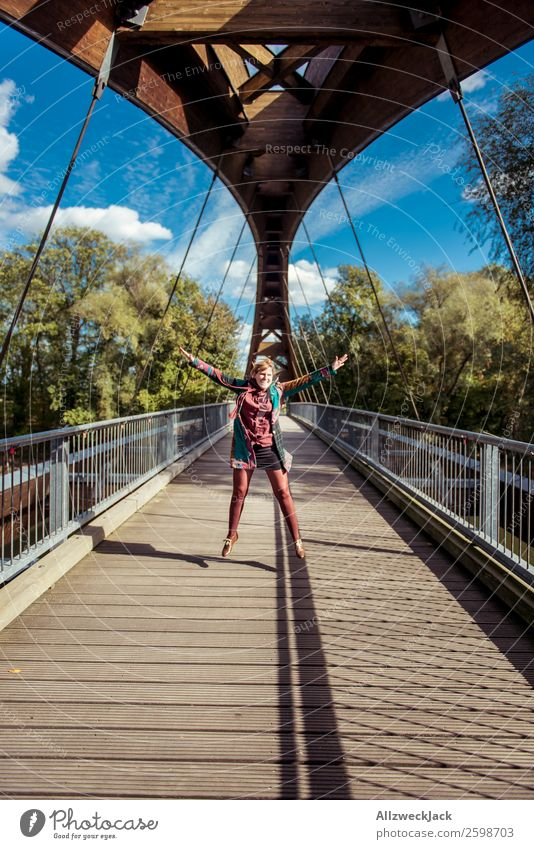 young woman jumps into the air on a wooden bridge 1 Person Young woman Beautiful weather Blue sky Clouds Happiness Free High spirits Jump Bridge Wooden bridge