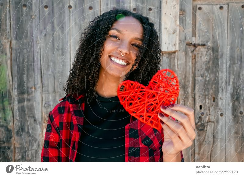 Beautiful young woman holding a red heart Woman Human being Youth (Young adults) Young woman Red Loneliness Joy Black 18 - 30 years Healthy Lifestyle Adults