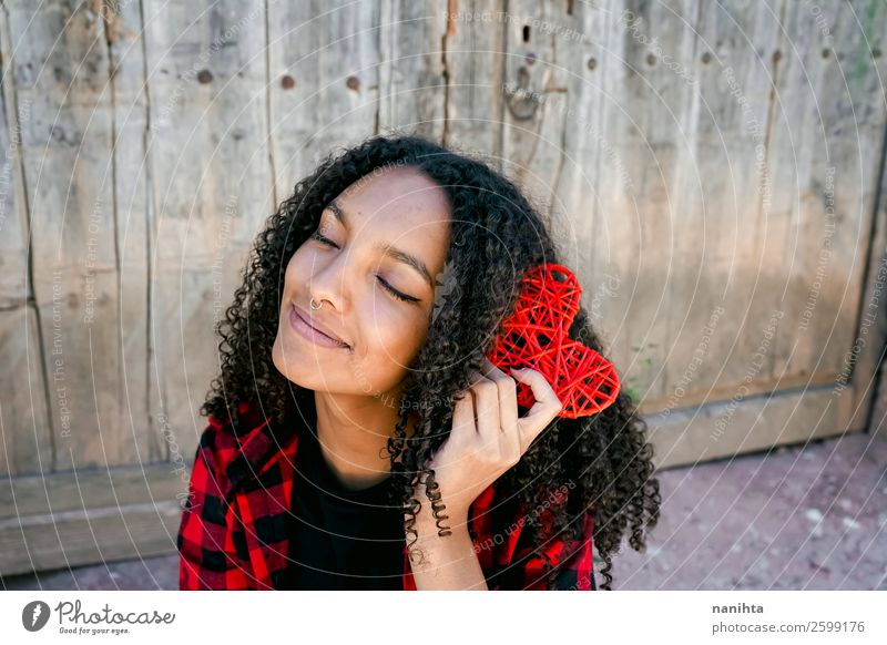 Beautiful young woman holding a red heart Lifestyle Style Joy Hair and hairstyles Healthy Wellness Harmonious Well-being Human being Feminine Young woman