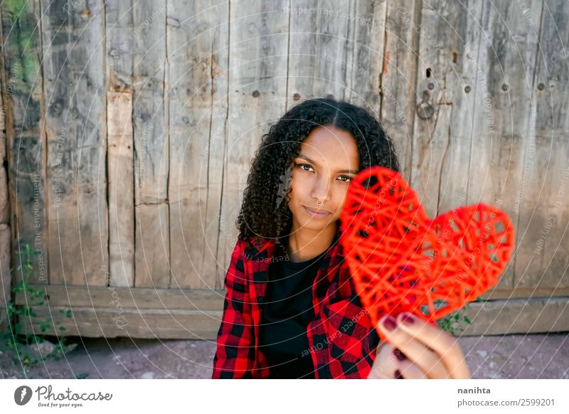 Beautiful young woman holding a red heart Woman Human being Youth (Young adults) Red Loneliness Joy Black 18 - 30 years Healthy Lifestyle Adults Love Natural
