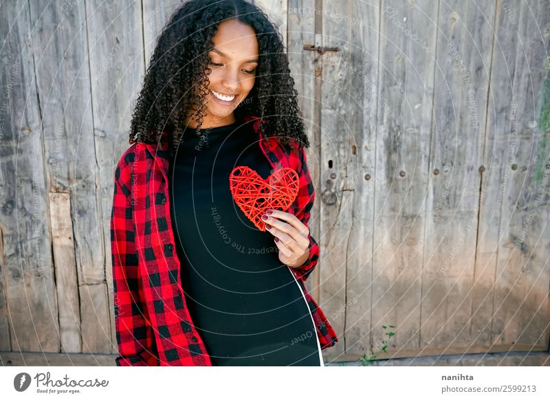 Beautiful young woman holding a red heart Lifestyle Style Joy Hair and hairstyles Human being Feminine Young woman Youth (Young adults) Woman Adults
