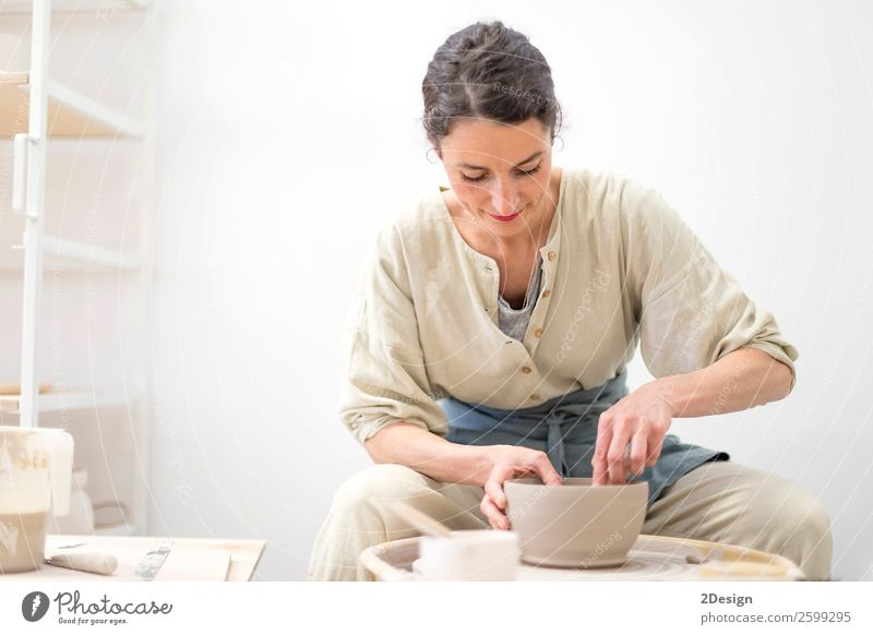 Young female sitting by table and making clay or ceramic Woman Human being Youth (Young adults) Young woman 18 - 30 years Adults Feminine Business Small