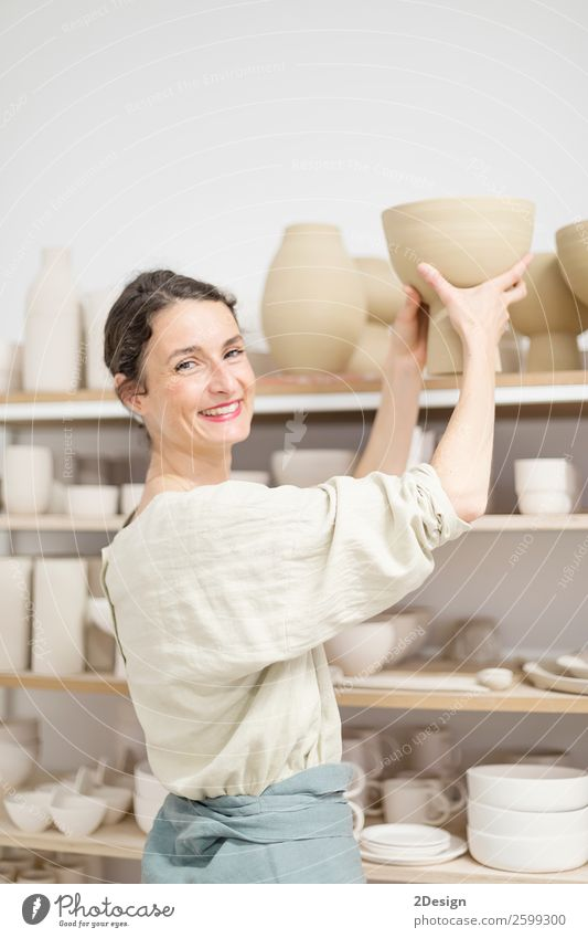 Beautiful ceramist owner looking to the camera while smiling Pot Leisure and hobbies Handcrafts Work and employment Profession Craftsperson Workplace Office