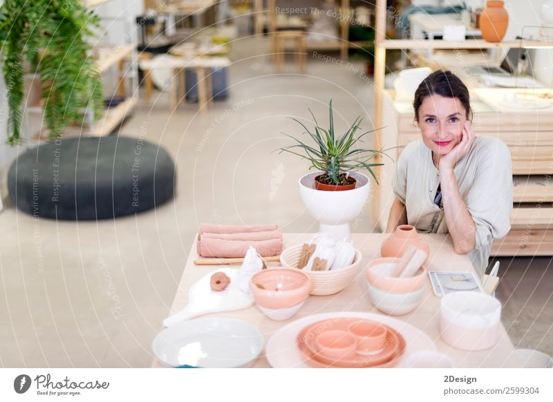 Woman in work wear in her workshop Crockery Leisure and hobbies Handcrafts Table Work and employment Profession Craftsperson Workplace Office Craft (trade)