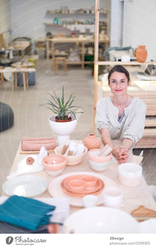 Woman in work wear in her workshop by table with handmade items Crockery Leisure and hobbies Handcrafts Table Work and employment Profession Craftsperson